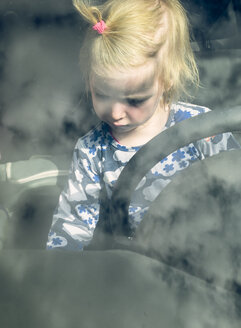 Blond toddler sitting behind steering wheel in a car - GSF001042