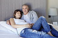 Happy man and pregnant wife relaxing on bed - LITF000122