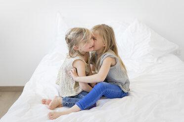 Girl whispering secret in the ear of her little sister - LITF000139