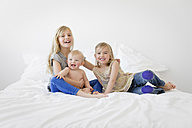 Three laughing siblings sitting on a  bed - LITF000142