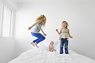 Two little sisters jumping on a bed while her baby brother watching them - LITF000145