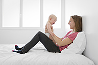 Mother sitting with her baby on a bed - LITF000148