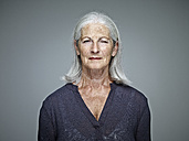 Portrait of senior woman with grey hair in front of grey background - RHF001111
