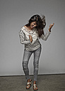 Excited young woman playing air guitar n front of grey background - RHF001120