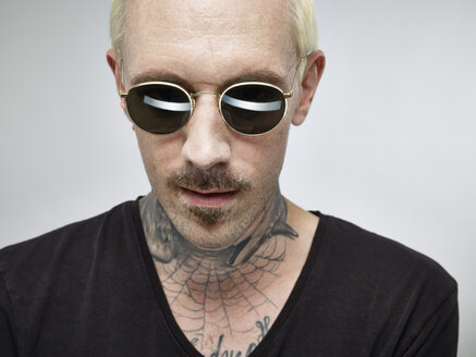 Portrait of man with tattoo and blond dyed hair wearing sunglasses - RHF001123