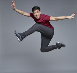 Portrait of young man jumping in the air in front of grey background - RHF001129