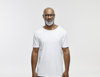 Portrait of smiling bald man with beard wearing spectacles and white t-shirt - RHF001132