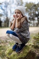 Portrait of smiling girl crouching on boulder - MGOF001164