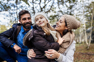 Happy parents with daughter in the forest - MGOF001167