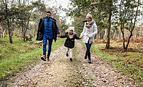 Happy parents with daughter walking on forest path - MGOF001173