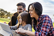 Happy parents with daughter using digital tablet outdoors - MGOF001179
