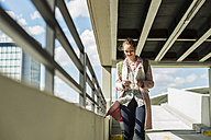 Young woman with earbuds and cell phone in parking garage - UUF006165