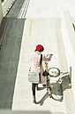 Young woman pushing bicycle on parking level - UUF006174