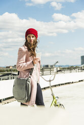 Young woman with bicycle holding cell phone - UUF006183
