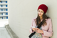 Young woman leaning against concrete wall looking at cell phone - UUF006186