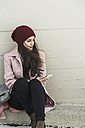 Young woman sitting at concrete wall holding cell phone - UUF006189