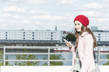 Smiling young woman outdoors holding cell phone - UUF006192