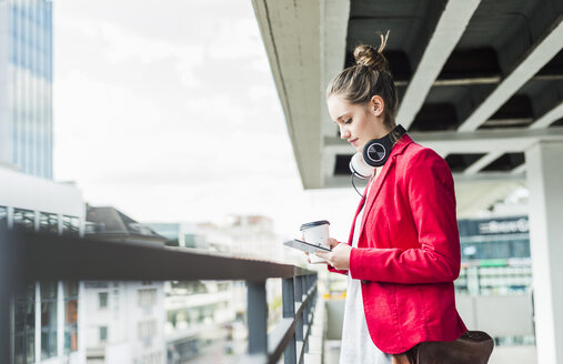 Young woman with coffee to go, headphones and phablet in parking garage - UUF006198