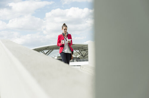 Young woman with coffee to go, headphones and phablet on parking level - UUF006201
