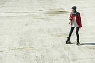 Young woman with cell phone and inline skates on parking level - UUF006207