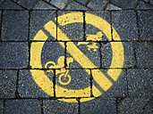 Yellow prohibition sign, riding bicycle and skateboarding on pavement - DISF002279