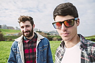 Portrait of smiling young man with his friend wearing mirrored sunglasses in the foreground - RAEF000719