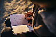 Young woman sitting on the beach using notebook, close-up - JRFF000229