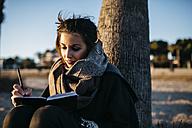 Spain, Tarragona, portrait of young woman using notebook - JRFF000232