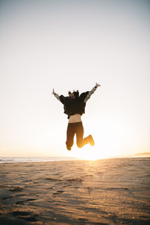 Young woman jumping in the air on the beach in winter - JRFF000241