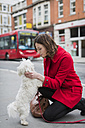 UK, London, young woman kneeling on pavement face to face to her dog - MAUF000145