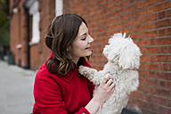 UK, London, smiling young woman  face to face to her dog - MAUF000148