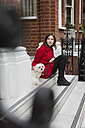 UK, London, young woman sitting on stairs besides her dog - MAUF000151