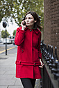 UK, London, portrait of young woman telephoning with smartphone  wearing red jacket - MAUF000154