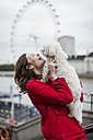 UK, London, happy young woman with dog on her arms and London Eye in the background - MAUF000157