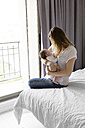 Young mother sitting on bed holding her sleeping newborn in her arms - LITF000159