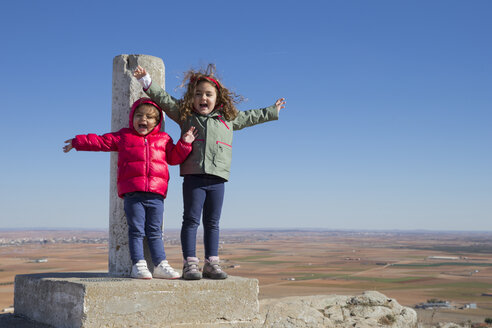Spain, Consuegra, two happy little girls standing on summit with arms outstretched - ERLF000090