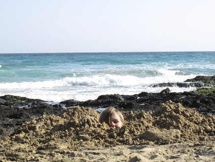 Spain, Canary Islands, Fuerteventura, boy at the sea buried in sand - TMF000082