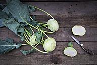 Organic kohlrabi on wood, knife, halved - LVF004315