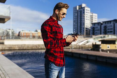 Ireland, Dublin, young man at city dock listening to music - BOYF000048