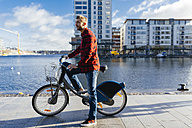 Ireland, Dublin, young man at city dock with city bike - BOYF000057