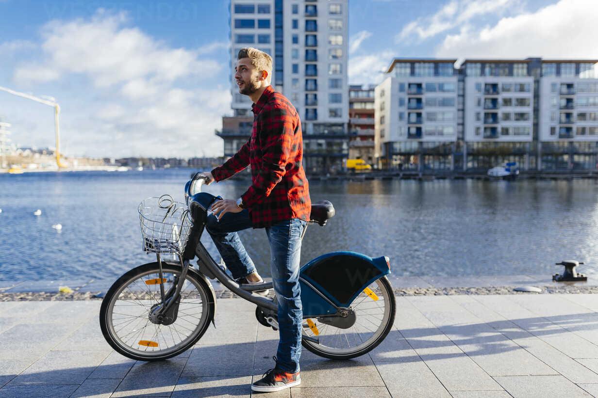 Ireland, Dublin, young man at city dock with city bike - BOYF000057 - Boy/Westend61