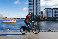 Ireland, Dublin, young man at city dock riding city bike - BOYF000060