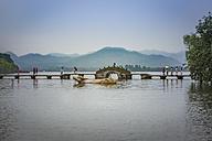 China, Zhejiang, Hangzhou, Giant golden water buffalo and pedestrians on a bridge at the West lake - NK000423