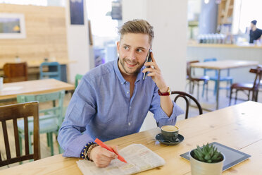 Man with newspaper sitting in a coffee shop telephoning with smartphone - BOYF000074