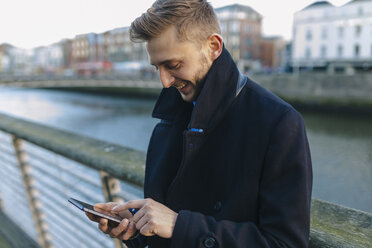 Ireland, Dublin, smiling young businessman looking at his smartphone - BOYF000080