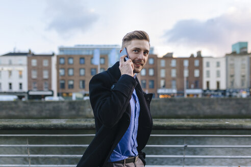 Ireland, Dublin, portrait of young businessman telephoning with smartphone - BOYF000083