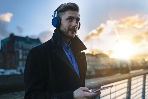 Ireland, Dublin, young man hearing music with headphones at twilight - BOYF000086