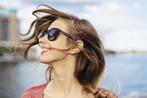 Portrait of smiling woman with blowing hair wearing sunglasses - BOYF000089