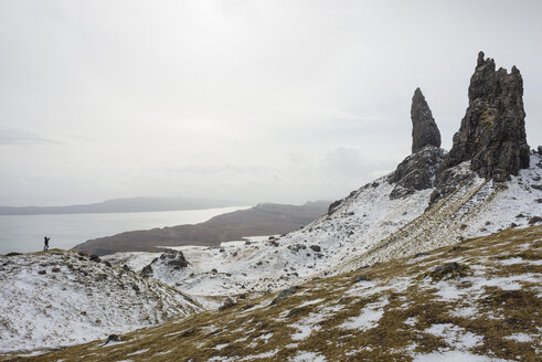 UK, Scotland, Isle of Skye, boy taking a photo of the snow-covered Old Man of Storr - JBF000252