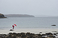 UK, Scotland, Isle of Skye, walking girl with umbrella at rainy and stormy beach - JBF000255